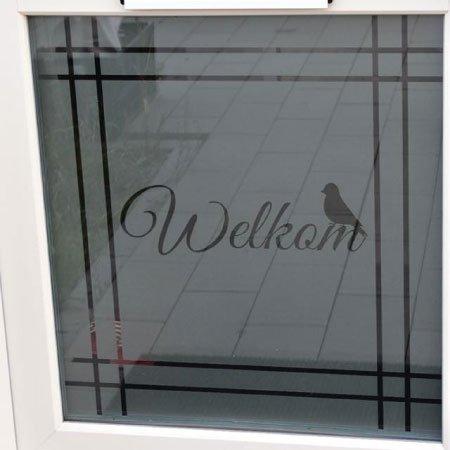 Raamfolie sticker voor de voordeur. Het woord welkom, een vogel en lijnen